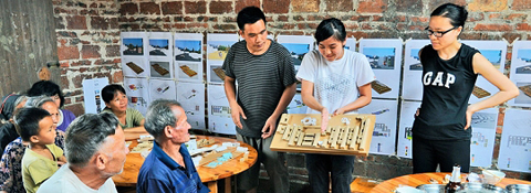 Students explaining the design models of village houses in Luk Zuk Village, China